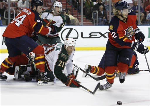 Minnesota Wild center Kyle Brodziak (21) can't get to the puck as Florida Panthers defenseman Erik Gudbranson (44) and Florida Panthers right wing Kris Versteeg (32) defend during the first period of an NHL hockey game, Thursday, Feb. 23, 2012, in Sunrise, Fla. (AP Photo/Lynne Sladky)