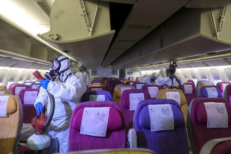 FILE PHOTO: Members of the Thai Airways crew disinfect the cabin of an aircraft of the national carrier during a procedure to prevent the spread of the coronavirus at Bangkok's Suvarnabhumi International Airport