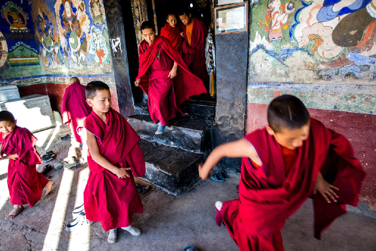Buddhist monks depart from morning prayers at the Thikse Monastery on October 5, 2012 near  Leh in Ladakh, India. The Thikse monastery is a Tibetan Buddhist monastery of the Yellow Hat (Gelugpa) sect, located on top of a hill, approximately 20 kilometres east of Leh. It is noted for its semblance to the Potala Palace in Lhasa, Tibet and is the largest monastery in central Ladakh. Ladakh, nestled between the Kunlun mountain range in the north and the main Great Himalayas to the south, was once an ancient Buddhist Kingdom and for over half a century now, a strategic military outpost for India. Ladakh, sharing borders with both China and Pakistan, has seen an increase in tourism over the last few years, an alternative to Nepali Himalayan treks. (Photo by Daniel Berehulak/Getty Images)