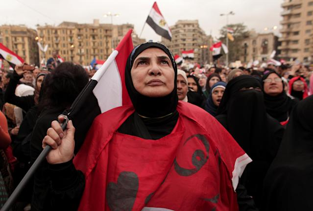 An Egyptian woman holds a national flag as she listens to speakers, not pictured, in Tahrir Square in Cairo, Egypt, Tuesday, Dec. 4, 2012. Hundreds of black-clad riot police deployed around the Itihadiya palace in Cairo's district of Heliopolis. Barbed wire was also placed outside the complex, and side roads leading to it were blocked to traffic. Protesters gathered at Cairo's Tahrir square and several other points not far from the palace to march to the presidential complex. (AP Photo/Maya Alleruzzo)