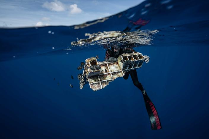 """Lecomte holds a piece of a plastic crate that's become a haven for fish and a home for other marine life. (Photo: <a href=""""https://www.instagram.com/p/BzLUm2QhDoC/?utm_source=ig_embed"""" rel=""""nofollow noopener"""" target=""""_blank"""" data-ylk=""""slk:@joshmunoz/The Vortex Swim"""" class=""""link rapid-noclick-resp"""">@joshmunoz/The Vortex Swim</a>)"""