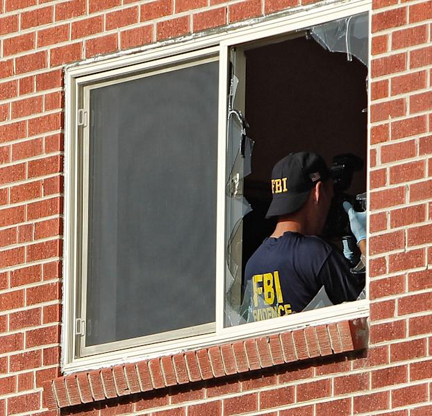 A FBI agent can be seen through the broken window of the apartment of shooting suspect James Eagen Holmes in Aurora, Colo. Federal agents began collecting evidence from the apartment after clearing it of booby traps, Saturday, July 21, 2012. Holmes has been charged in the shooting at an Aurora theatre early Friday that killed twelve people and injured 59.(AP Photo/Ed Andrieski)