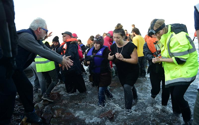 A man holds out his hands to a woman wading through water after her arrival on the Greek island of Lesbos after crossing the Aegean Sea from Turkey on November 19, 2015