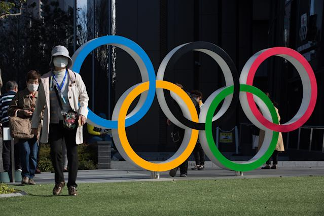 Women with surgical masks walk next to the Olympic Rings in front of the Japan Olympic Museum in Shinjuku. (Photo by Stanislav Kogiku/SOPA Images/LightRocket via Getty Images)