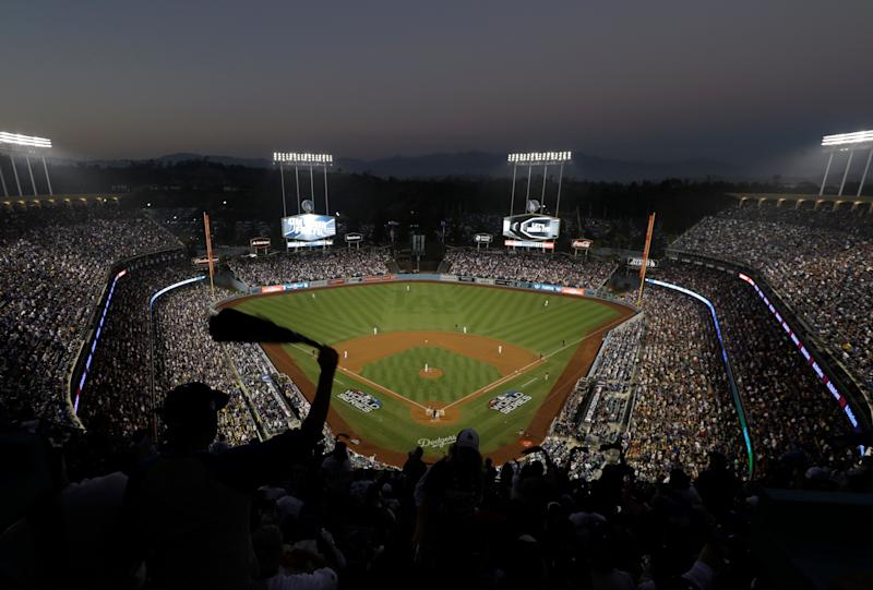 Fans cheer from the top of Dodger Stadium during Game 4 of the World Series baseball game between the Boston Red Sox and Los Angeles Dodgers on Saturday, Oct. 27, 2018, in Los Angeles. (AP Photo/Elise Amendola)