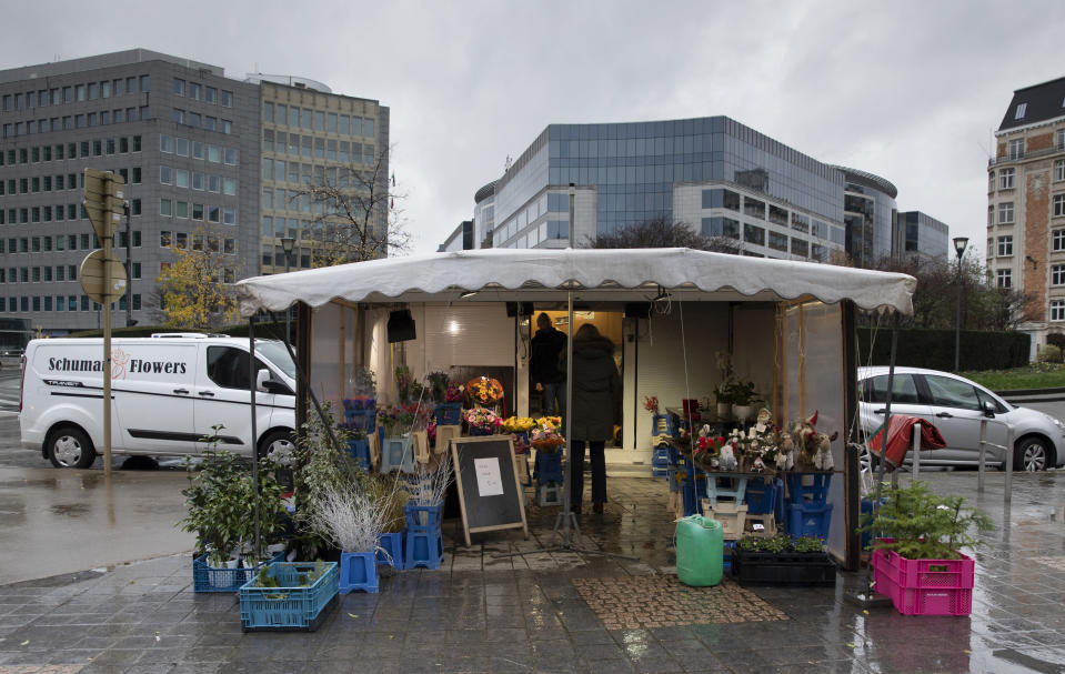 A woman talks to a flower seller outside EU headquarters in Brussels, Thursday, Dec. 24, 2020. European Union and British negotiators worked through the night and into Christmas Eve in the hopes of putting the finishing touches on a trade deal that should avert a chaotic economic break between the two sides on New Year's Day. (AP Photo/Virginia Mayo)