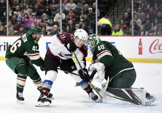 Minnesota Wild goaltender Devan Dubnyk (40) stop s shot by Colorado Avalanche's Matt Calvert (11) with help from Minnesota Wild's Jared Spurgeon (46) during the second period of an NHL hockey game Sunday, Feb. 9, 2020, in St. Paul, Minn. Spurgeon was called for a penalty on the play. (AP Photo/Hannah Foslien)