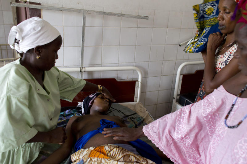 In this May 24, 2012 photo, midwife Sabado Sambu, left, checks on Fatumata Djau, 32, while family members comfort her and fan her with a cloth, after Djau began convulsing at the regional hospital in Gabu, Guinea-Bissau. Family members brought Djau to the hospital after discovering that she had given birth alone in her bedroom and was suffering from complications. After initial treatment, the medical staff believed her to be out of danger, but twelve hours after arriving at the hospital Djau began convulsing and died soon after. She left behind four daughters - including her healthy newborn - a distraught family, and an elderly widower. In Guinea-Bissau, one of the deadliest places in the world to give birth, a woman has a 1 in 19 chance of maternal death, compared to about 1 in 2,100 in the United States. Experts say women are increasingly heading to medical centers when things go awry, but logistical, financial, and cultural barriers are still keeping many pregnant women from seeking help in time. (AP Photo/Rebecca Blackwell)