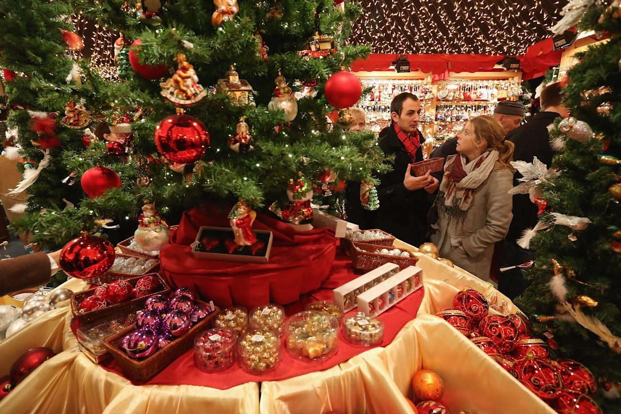 BERLIN, GERMANY - NOVEMBER 26:  Visitors look at Christmas decorations for sale at the Kaethe Wohlfahrt stand at the annual Christmas market at Gendarmenmarkt on its opening day on November 26, 2012 in Berlin, Germany. Christmas markets, with their stalls selling mulled wine, Christmas tree decorations and other delights, are an integral part of German Christmas tradition, and many of them opened across Germany today.  (Photo by Sean Gallup/Getty Images)