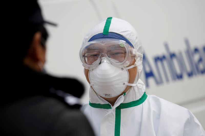 FILE PHOTO: A hospital staff member in protective garments talks to a police officer at a checkpoint to the Hubei province exclusion zone at the Jiujiang Yangtze River Bridge in Jiujiang