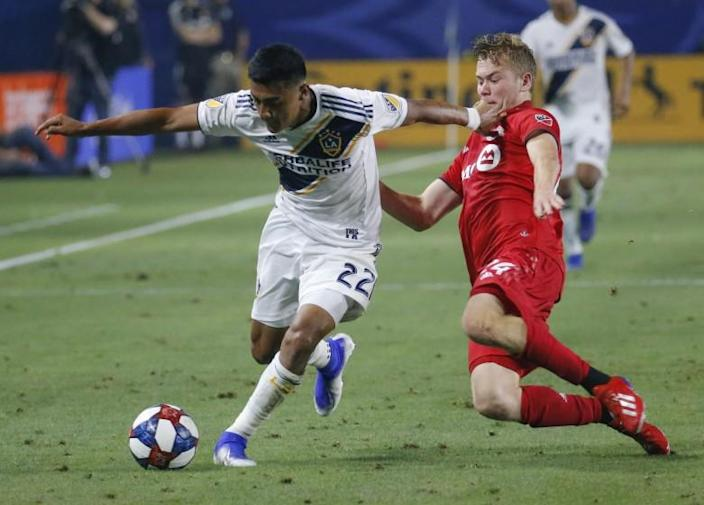 LA Galaxy defender Julian Araujo (22) and Toronto FC midfielder Jacob Shaffelburg (24), vie for the ball during an MLS soccer match in Carson, Calif., Thursday, July 4, 2019. The Galaxy won 2-0. (AP Photo/Ringo H.W. Chiu)