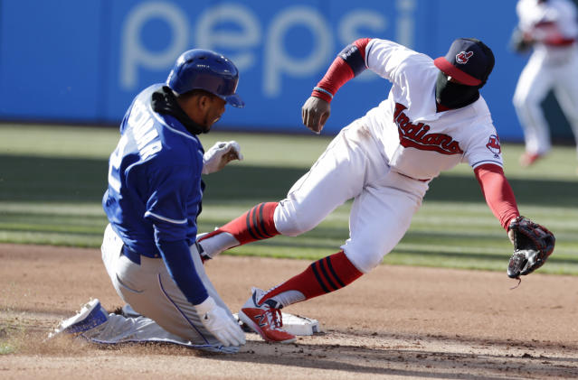 Kansas City Royals' Alcides Escobar, left, slides safely into second base as Cleveland Indians' Francisco Lindor reaches but can't get to the ball in the fifth inning of a baseball game, Saturday, April 7, 2018, in Cleveland. Escobar advanced to third base on an error by Indians catcher Roberto Perez. (AP Photo/Tony Dejak)