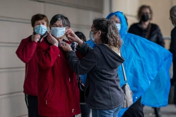 People are pictured lined up to receive their COVID-19 vaccination at an immunization clinic in the Fraser Health region of Surrey, British Columbia on Wednesday, March 24, 2021.  (Ben Nelms/CBC - image credit)