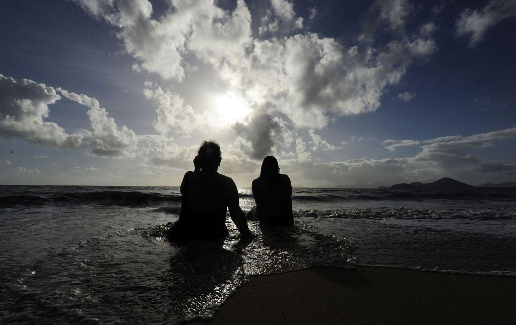 Spectators watch the solar eclipse while sitting in the surf in Palm Cove, Australia.