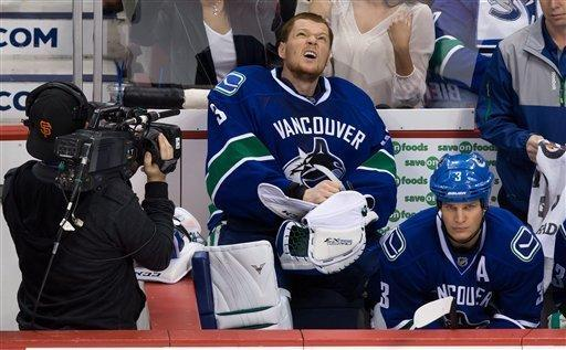 Vancouver Canucks goalie Cory Schneider, center, sits on the bench next to teammate Kevin Bieksa, right, after he was replaced by Roberto Luongo after allowing five goals to the Anaheim Ducks, in an NHL hockey game in Vancouver, British Columbia, on Saturday, Jan. 19, 2013. (AP Photo/The Canadian Press, Darryl Dyck)