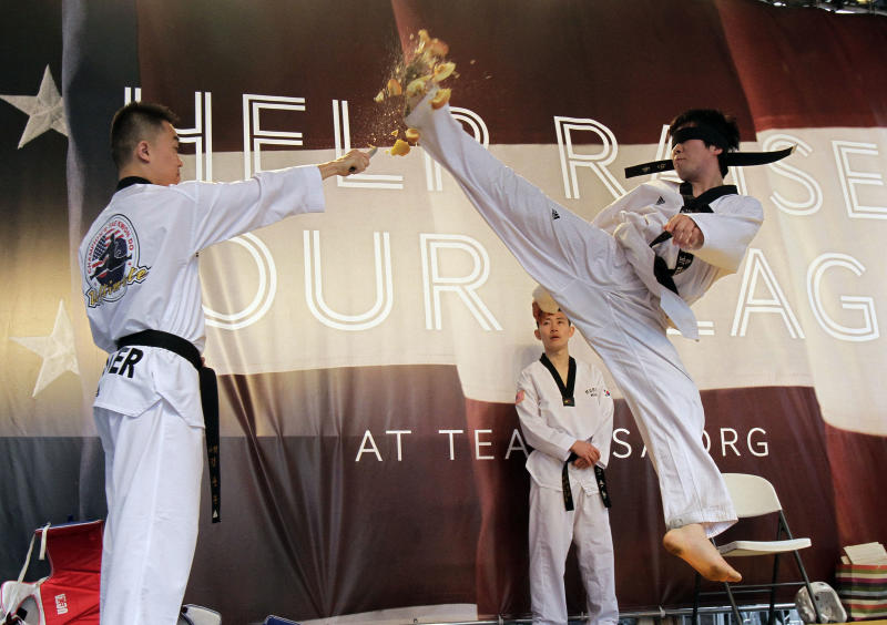 Members of the New York State Taekwondo Federation demonstrate the sport on stage in New York's Times Square during U.S. Olympic Team festivities, Wednesday, April 18, 2012. The event marks 100 days until the London Olympics. (AP Photo/Richard Drew)