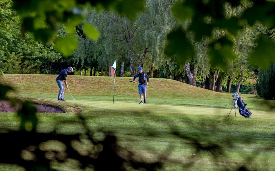 Golfers putt on the 9th green at Allerton Manor golf course in Liverpool after the lifting of lockdown restrictions - PA
