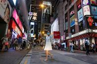 FILE PHOTO: A woman crosses a street in the Central business district in Hong Kong, China