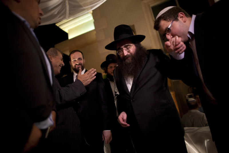 FILE - In this July 11, 2011 file photo, a man kisses the hand of Rabbi Yoshiyahu Pinto at a wedding in Lod, central Israel. Rabbi Pinto has been placed under house arrest and banned from traveling abroad, as police investigate suspicions that he bribed a high-ranking officer for access to his police file.  (AP Photo/Oded Balilty, File)