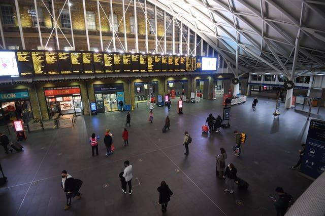 Travellers wait for trains on the concourse at King's Cross station in central London (Victoria Jones/PA)