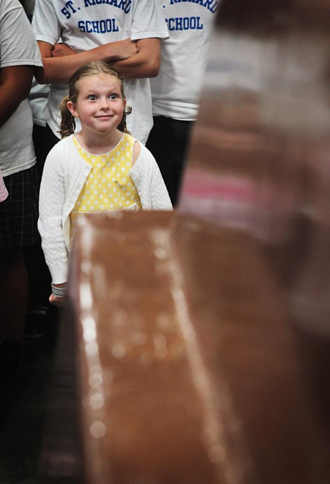 CHICAGO, IL - SEPTEMBER 13: Lexi Jeffrey looks over a 12,290 pound chocolate bar created by the World's Finest Chocolate company to set a Guinness World Record September 13, 2011 in Chicago, Illinois. The bar, which stands nearly 3 feet high and measures 21 feet long, beat the previous record chocolate bar by more than a ton.  (Photo by Scott Olson/Getty Images)