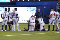Atlanta Braves gather around right fielder Ronald Acuna Jr., lying on his back, after he attempted to walk after trying to make a catch on an inside-the-park home run hit by Miami Marlins' Jazz Chisholm Jr. during the fifth inning of a baseball game Saturday, July 10, 2021, in Miami. (AP Photo/Lynne Sladky)