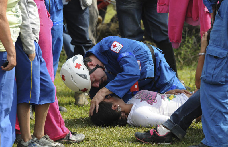 "A paramedic attends a woman who fainted while waiting outside the ""El Desespero"" coal mine for news of trapped miners in Angelopolis, Colombia, Thursday March 8, 2012. At least four miners died while five others are still missing after miners hit a source of water Wednesday that flooded and collapsed the small mine on Wednesday.  (AP Photo/Luis Benavides)"