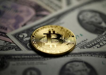 A Bitcoin and Dollar notes are seen in this illustration picture
