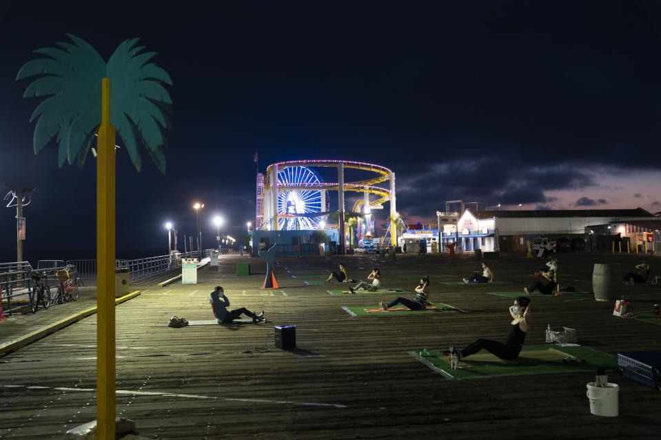 """Barre instructor Danielle Lew, left, leads an outdoor class on the Santa Monica Pier in Santa Monica, Calif., Monday, Oct. 19, 2020. """"I'm going to vote for Biden and Harris,"""" said the 35-year-old fitness instructor. """"The current administration has shown they cannot make choices that are beneficial to the American people, and we need someone who will make those choices thinking of everyone."""" (AP Photo/Jae C. Hong)"""