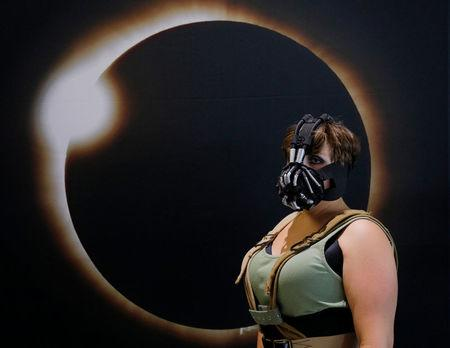 Cassie Gillard, from bay City Michigan and dressed as Lady Bane from the Batman franchise, poses for a photograph in front of an image of a solar eclipse at the Eclipse Comic-Con at Southern Illinois University in Carbondale, Illinois, U.S., August 20, 2017 one day before a total solar eclipse in the city.   REUTERS/Brian Snyder