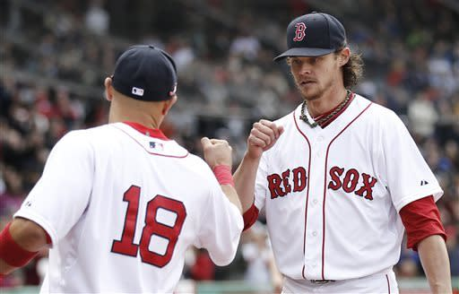 Boston Red Sox starting pitcher Clay Buchholz fist bumps with Shane Victorino (18) while leaving the field after losing his no hitter the eighth inning of a baseball game against the Tampa Bay Rays at Fenway Park in Boston Sunday, April 14, 2013. (AP Photo/Winslow Townson)