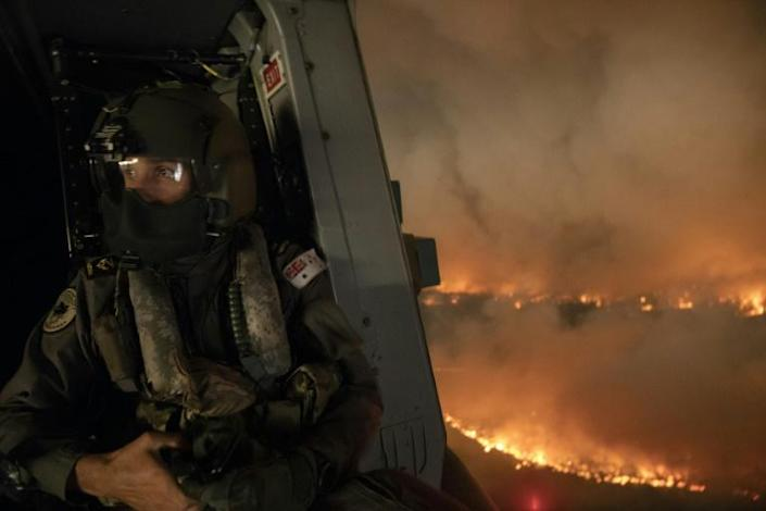 An Australian defence forces member monitors the Tianjara fire from a helicopter over the Moreton and Jerrawangala National Parks area in New South Wales (AFP Photo/CPOIS Kelvin HOCKEY)