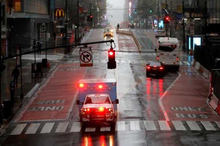 FILE PHOTO: Ambulance in heavy rain and high winds across nearly empty East 42nd street during outbreak of coronavirus disease (COVID-19) in New York