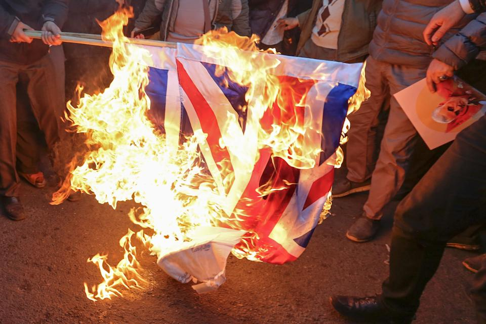 """Iranian demonstrators set alight a Union Jack in front of the British embassy in Iran's capital Tehran on January 12, 2020 following the British ambassador's arrest for allegedly attending an illegal demonstration. - Chanting """"Death to Britain"""", up to 200 protesters rallied outside the mission a day after the brief arrest of British ambassador Rob Macaire at a memorial for those killed when a Ukraine airliner was shot down. (Photo by ATTA KENARE / AFP) (Photo by ATTA KENARE/AFP via Getty Images)"""