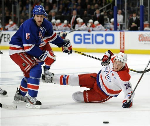 New York Rangers' Dan Girardi, left, checks Washington Capitals' John Carlson off the puck during the second period of an NHL hockey game on Saturday, April 7, 2012, at Madison Square Garden in New York. (AP Photo/Bill Kostroun)