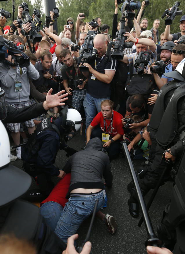 Polish riot police detain a soccer fan prior to the Euro 2012 Group A soccer match between Poland and Russia in Warsaw, Poland , Tuesday, June 12, 2012. (AP Photo/Czarek Sokolowski)