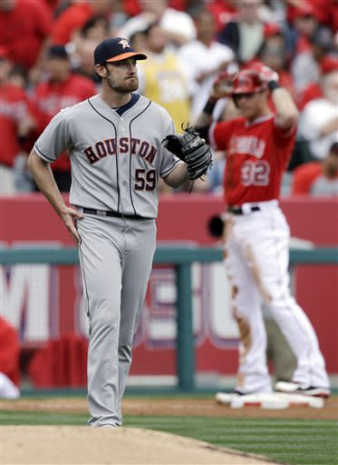 Houston Astros pitcher Philip Humber returns to the mound after Los Angeles Angels' Josh Hamilton, background, tripled in the third inning of an interleague baseball game in Anaheim, Calif., Sunday, April 14, 2013. (AP Photo/Reed Saxon)