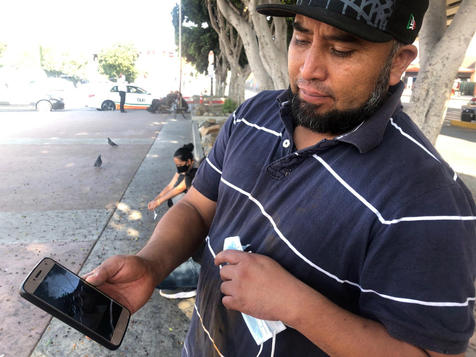José Edgar Zuleta shows a photo in Tijuana, Mexico, of his 21-year-old on Oct. 9, 2020. Zuleta, whose business selling religious jewelry in the Mexican city of Puebla dried up when the pandemic hit, climbed Trump's 30-foot (9-meter) wall with a special ladder. He moved through brush in a heavily patrolled area for about a half-hour with two women before getting caught. His son, who cleared the wall ahead of him, got picked up hours later. (AP Photo/Elliot Spagat)