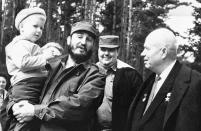 <p>Fidel Castro, Cuban prime minister, holds Soviet Premier Nikita Khrushchev's grandson Ivan Adzhubei in his arms as the visitor from Cuba spent a day at Khrushchev's country house on the outskirts of Moscow, April 30, 1963. The Soviet leader, a coat over his shoulders, looks on. An unidentified member of the Castro party is in the rear. (AP Photo/TASS) </p>