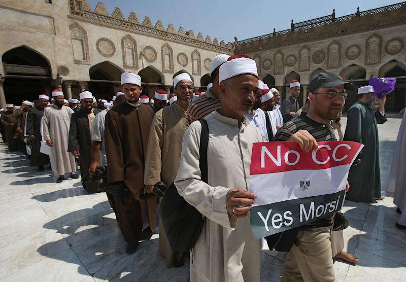 """An Egyptian cleric and a supporter of ousted Egypt's President Mohammed Morsi hold up a placard against Egyptian Defense Minister General Abdul Fatah al-Sisi, as they leave with other clerics following a protest, at al-Azhar mosque in Cairo, Egypt, Sunday, July 14, 2013. Egypt's military chief has defended the ouster of the Islamist president, saying he acted upon the will of the people after the """"stumbling"""" of the former government. (AP Photo/Hussein Malla)"""