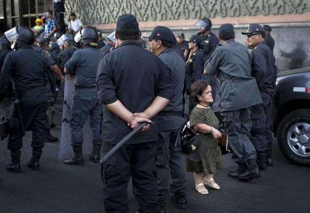 <p>A woman walks amid riot policemen during a protest organized by artisanal and small-scale gold miners in Lima, Peru, March 24, 2014. The miners marched in the country's capital for the fifth day, asking the government to repeal regulations aimed at formalizing informal miners. (Photo: Rodrigo Abd/AP) </p>