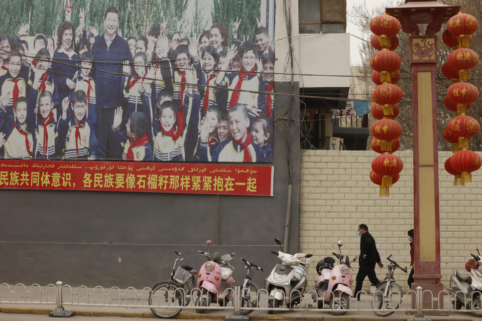 Residents walk past a propaganda board showing Chinese President Xi Jinping with local children and slogans calling for unity amongst the different ethnicities in Shule county in northwestern China's Xinjiang Uyghur Autonomous Region on March 20, 2021. Four years after Beijing's brutal crackdown on largely Muslim minorities native to Xinjiang, Chinese authorities are dialing back the region's high-tech police state and stepping up tourism. But even as a sense of normality returns, fear remains, hidden but pervasive. (AP Photo/Ng Han Guan)