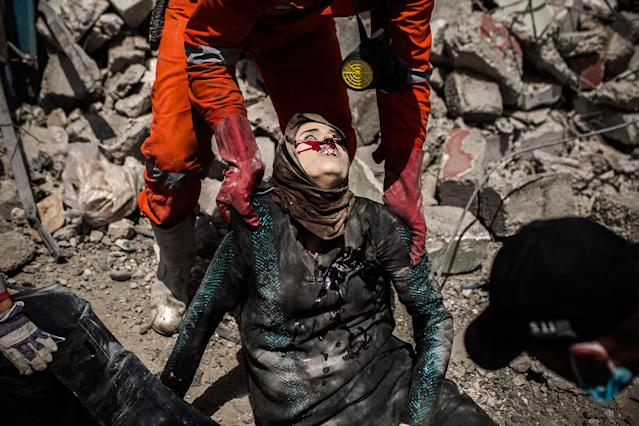 <p>A civil defense team holds the dead body of an Iraqi woman killed after a female suicide bomber blows herself up in Mosul, just a few meters far away from Al Noor Mosque. West Mosul. Iraq. July 2, 2017. (Photograph by Diego Ibarra Sánchez / MeMo) </p>