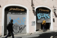 A man opens the shutter of a Restaurant in Rome, Friday, April 9, 2021. Italy has seen a stabilizing of the new variant-fueled infections over the past three weeks, though its daily death count remains stubbornly high, averaging between 300-500 COVID-19 victims per day, and its ICU capacity for virus patients is well over the threshold set by the government. (AP Photo/Gregorio Borgia)