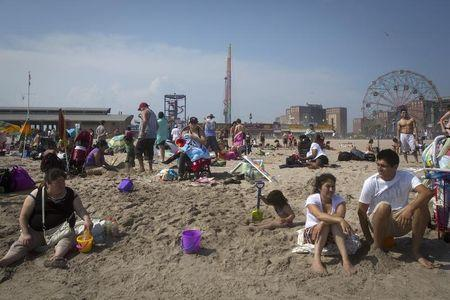 People sit on the beach at Coney Island in the Brooklyn borough of New York, July 2, 2014. REUTERS/Carlo Allegri