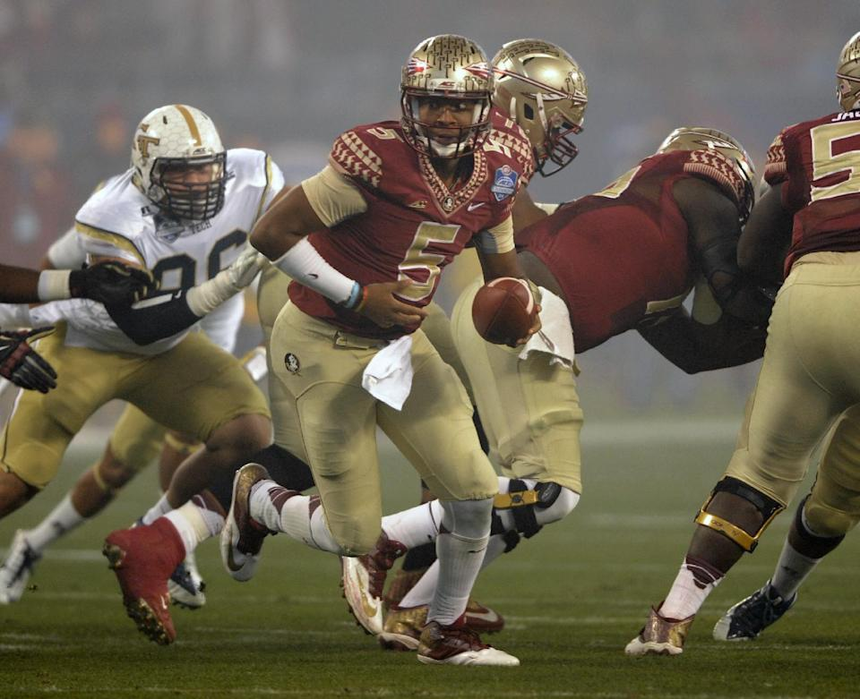 Florida State quarterback Jameis Winston (5) looks to hand off the ball against Georgia Tech during the first half of the Atlantic Coast Conference championship NCAA college football game in Charlotte, N.C., Saturday, Dec. 6, 2014. (AP Photo/Mike McCarn)