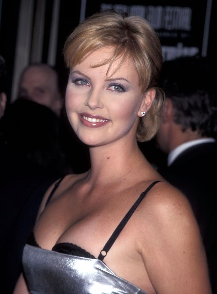 <p>At the 36th Annual New York Film Festival, Theron wears a half up do with swept over bangs and a charcoal grey smoky eye. (1998)</p>