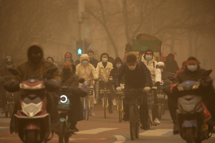 People ride bicycles across an intersection amid a sandstorm during the morning rush hour in Beijing, Monday, March 15, 2021. The sandstorm brought a tinted haze to Beijing's skies and sent air quality indices soaring on Monday. (AP Photo/Mark Schiefelbein)