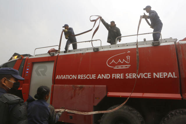 <p>Nepalese firemen work at the site after a passenger plane from Bangladesh crashed at the airport in Kathmandu, Nepal, March 12, 2018. (Photo: Niranjan Shreshta/AP) </p>
