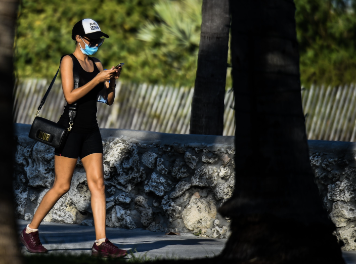 A woman wears a mask as she walks on Ocean Drive in South Beach, Miami, amid fears over the spread of the novel coronavirus (COVID-19) on March 31, 2020. (Photo: CHANDAN KHANNA/AFP via Getty Images)